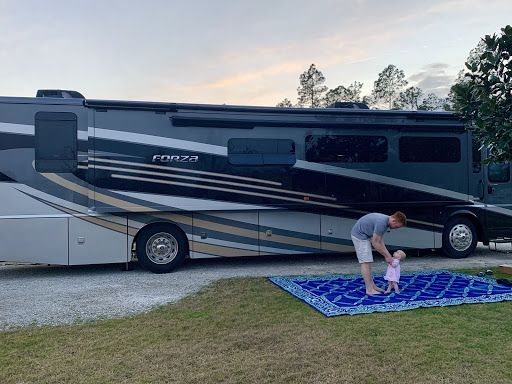 Heath with baby outside of their RV