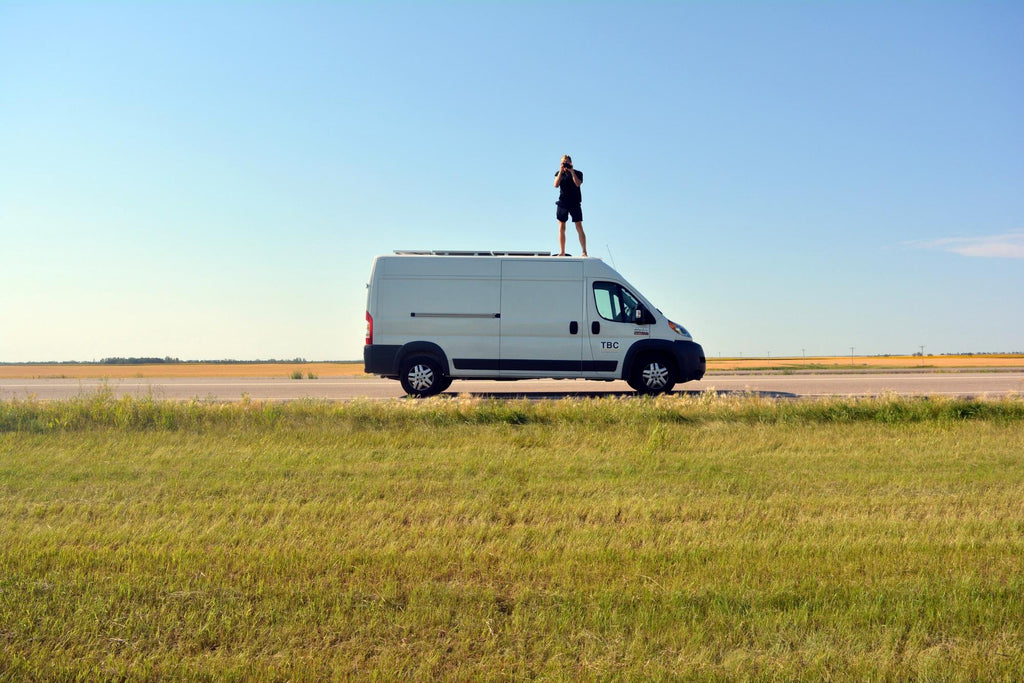 Mikah standing on top of his Ram promaster called Vanny