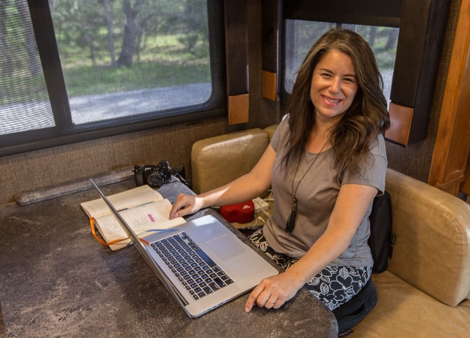 Digital nomad Camille working on her laptop in the RV