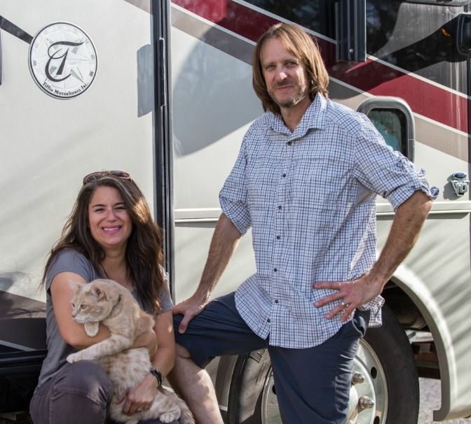Bryce and Camille with their cat in front of the RV
