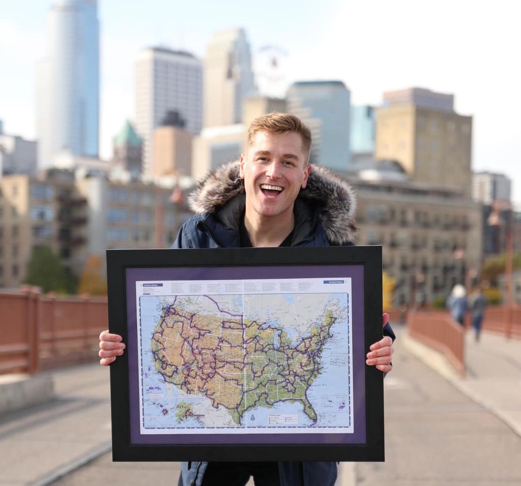 Mikah standing on the street with a map of all the places he has traveled to