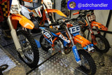 Three dirt bikes securely loaded in the back of a toy hauler using the Bike Binderz motor cycle tie down system