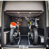 Two dirt bikes securely loaded in the back of a toy hauler using the Bike Binderz dirt bike kit