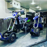 Two snow bikes securely fastened in the back of a toy hauler using the Bike Binderz securement device