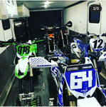 five snow bikes securely fastened into the back of an enclosed trailer using the Bike Binderz Snowbike Kit