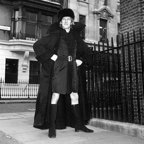 Michael Fish wearing a man-dress and full-length leather maxi-coat