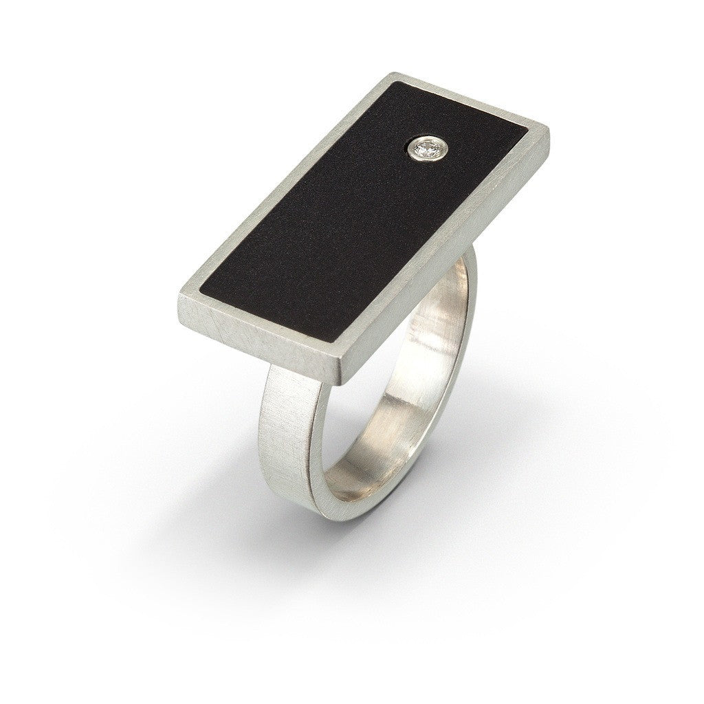 Modern design ring with side profile of black LEGO brick with diamond set flush into it.