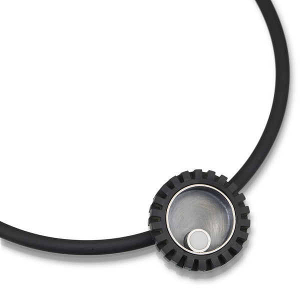 LEGO tire pendant with accents of silver and a white LEGO piece to create modern art jewelry