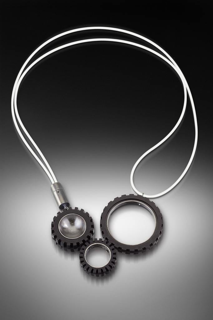 Contemporary and modern necklace with LEGO truck tires. Hand fabricated sterling silver  with patina and photo-etching finish