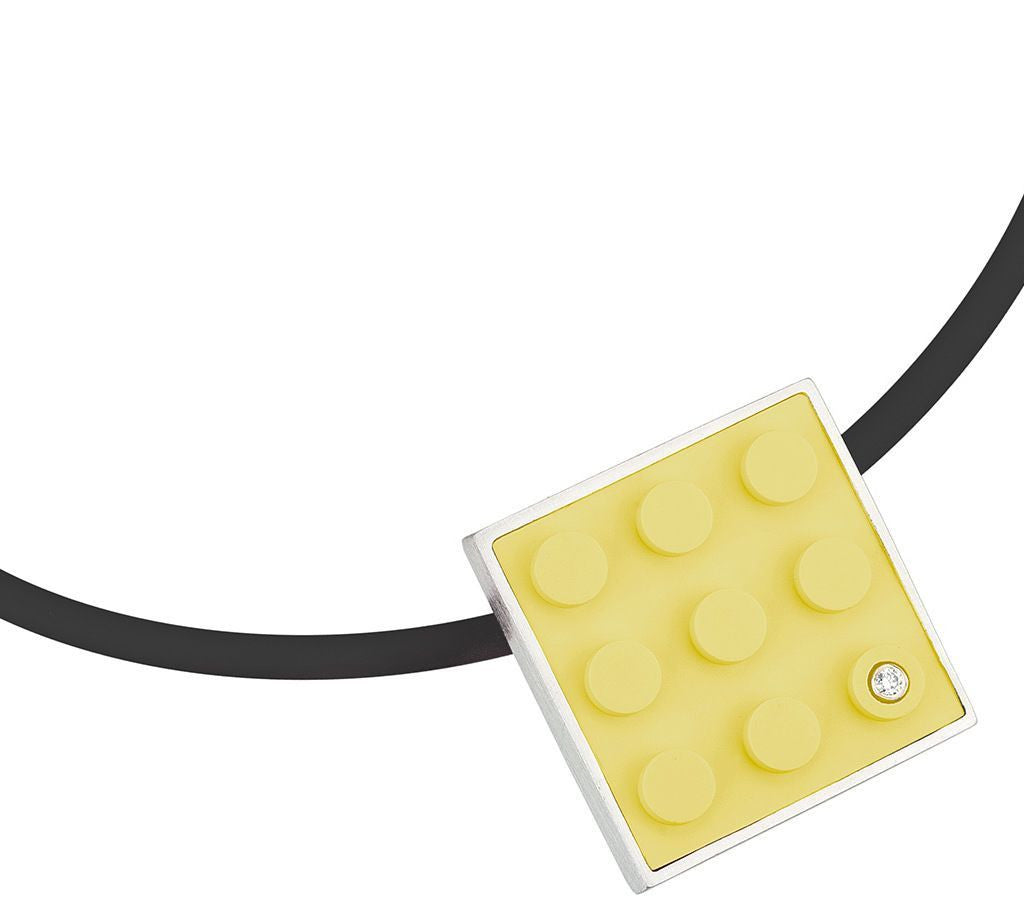 Yellow LEGO plate made into pendant with diamond set into sterling silver on rubber cord