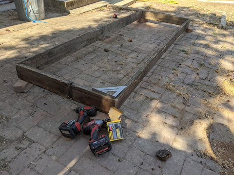 framework of DIY raised bed beside electric drill and screws