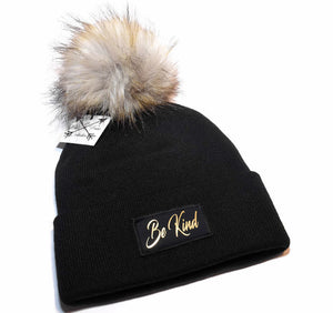Be Kind Beanie Toque. Hat is black with a gold graphic patch and large faux fur pom pom