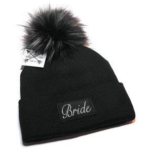 Bride Beanie Toque. Winter hat is black with a sparkly silver graphic patch and faux fur pom pom