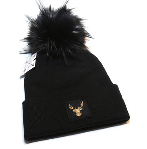 Deer beanie toque. Hat is black with a sparkly gold deer patch and a faux fur pom pom