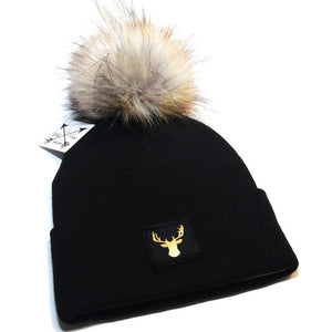 Deer beanie toque. Hat is black and a gold foil deer patch and a large faux fur pom pom