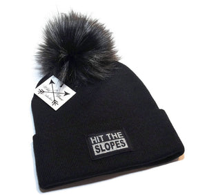Hit The Slopes beanie toque. Hat is black with a sparkly silver graphic Hit The Slopes and faux fur pom pom
