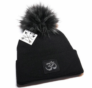 Om beanie toque in black and charcoal with large faux fur pom pom