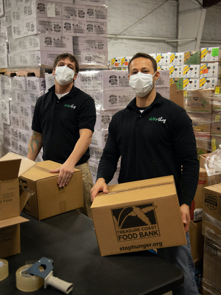 Two Bug Bite Thing employees build food and hygiene boxes for Treasure Coast Food Bank