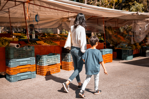 Young mother walks with child through outdoor market.