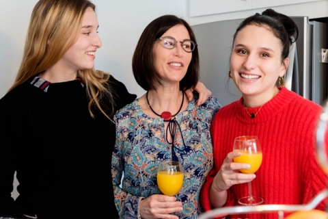 Two younger ladies surround an older woman holding mimosas.