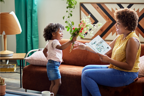 Young child hands bouquet of flowers to older woman holding a Mother's Day card.