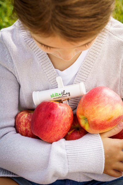 Girl holding a bunch of apples with a Bug Bite Thing