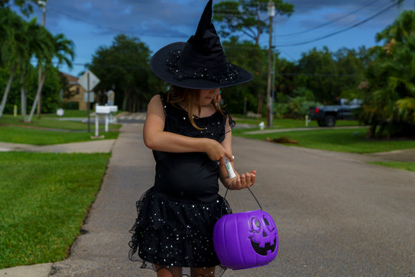 Girl dressed as witch using a Bug Bite Thing on Halloween