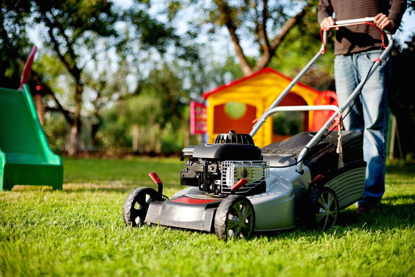 Photo of man mowing the lawn in backyard.