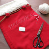 Personalising the Santa sack in white thread