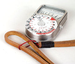 Attaching strap to light meter. Leather neck strap. Light brown leather black wrap.