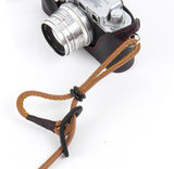 How to adjust an adjustable neck strap. Dark brown leather buckle on light brown adjustable neck strap.