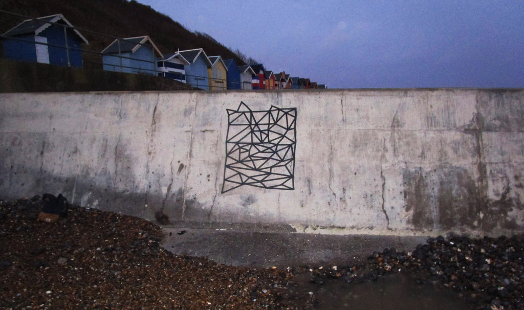 DESIGNING WITH TAPE ON A SEA WALL AT NIGHT