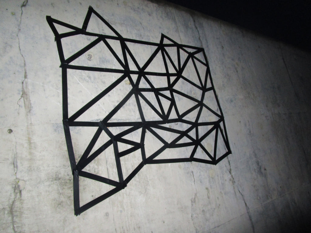Dabatag design on beach wall in Norfolk with black tape