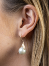 Hanging pearl earring on gold bloom