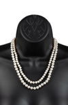 An image of a graduated double-strand white freshwater cultured pearl necklace on a black mannequin