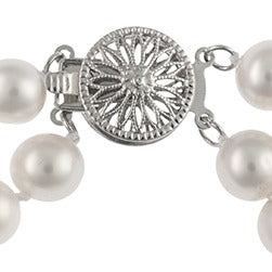 A close-up of a two-strand white pearl bracelet with a decorative silver starburst clasp