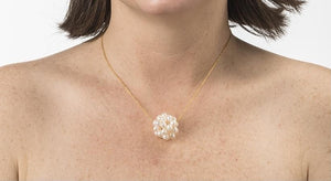 An image of a white snowball pearl cluster necklace on a gold chain on a woman's neck