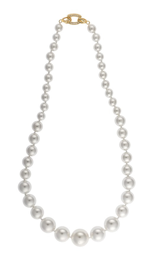 An image of a white pearl necklace with a decorative gold and crystal clasp