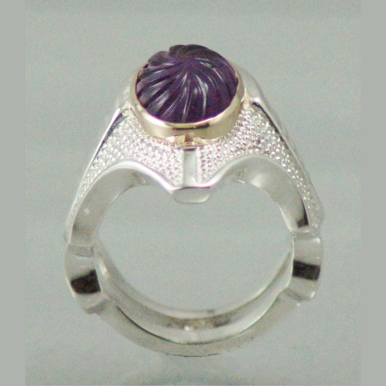 sterling silver ring set with a carved amethyst