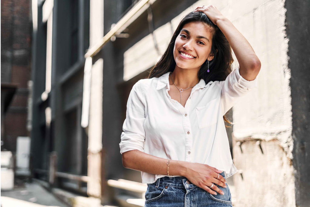woman wearing shirt and jeans, dangling earrings