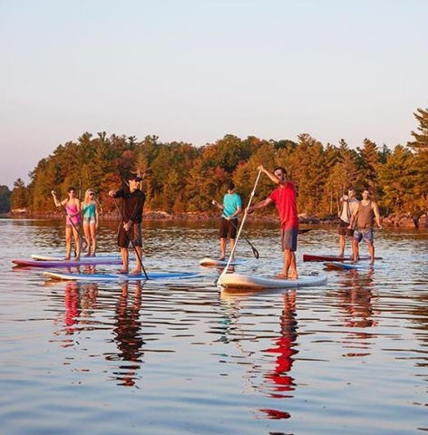 a group of stand up paddle boarders
