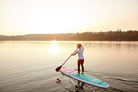 a female paddle boarder on a lake