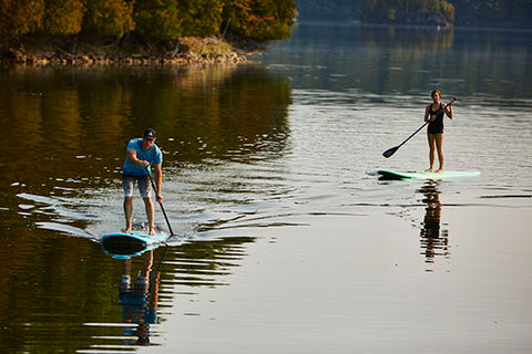A SUP user paddling a planing hull paddle board