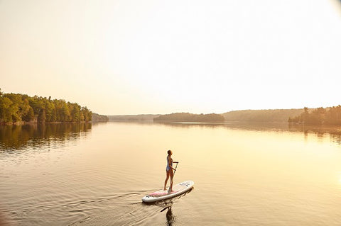 A stand up paddle boarder in very calm water