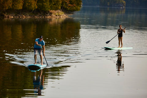 A couple stand up paddle boarding on a lake