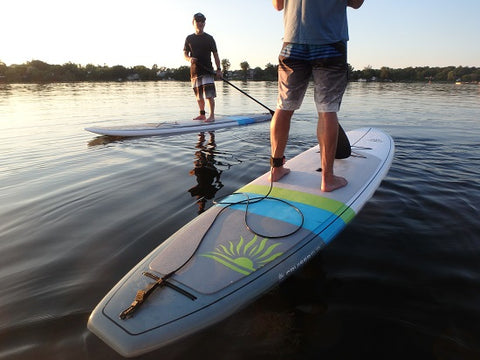stand up paddle boarders wearing a leashes
