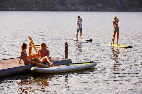 paddle boarders on a lake at sunset