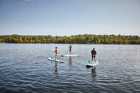 A family stand up paddle boarding on a lake