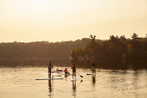 A family SUP'ing on a lake