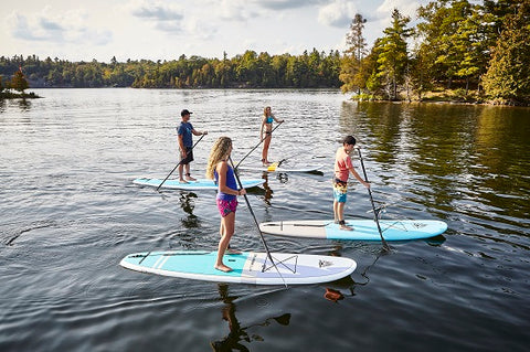 A family stand up paddle boarding